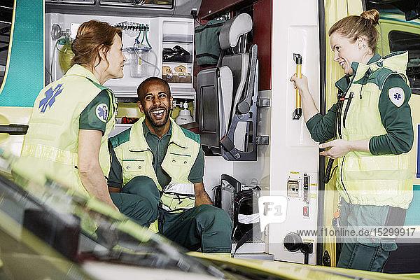 Fröhliche multiethnische Rettungssanitäter reden  während sie im Krankenwagen auf dem Parkplatz sitzen