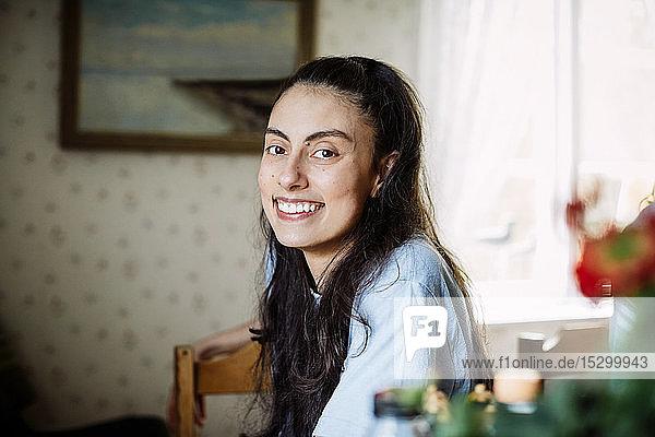 Porträt einer lächelnden jungen Frau mit langen Haaren  die zu Hause auf einem Stuhl sitzt