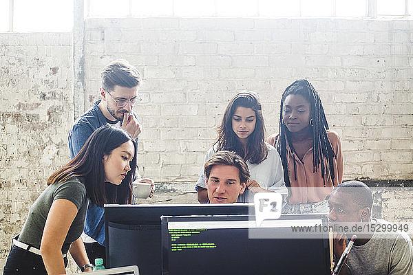 Seriöse Computerprogrammierer schauen beim Brainstorming am Arbeitsplatz auf den Computerbildschirm