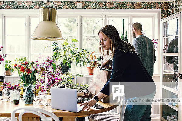 Woman using laptop at table while man gardening in room