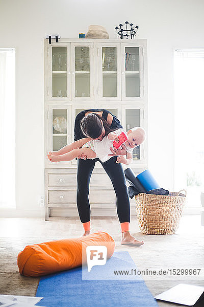 Verspielte berufstätige Mutter  die ein Mädchen austrägt  während sie zu Hause im Wohnzimmer Sport treibt