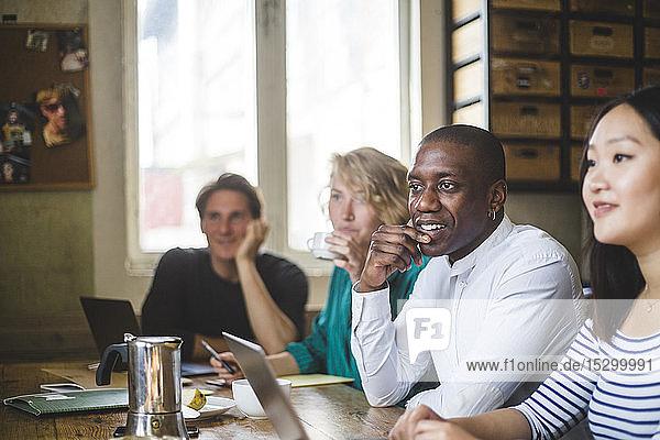 Zuversichtliche junge IT-Experten schauen weg  während sie am Schreibtisch in einem kreativen Arbeitsplatz sitzen