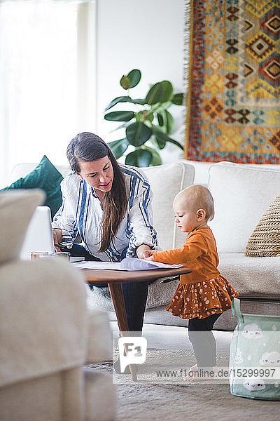Berufstätige Mutter spricht mit liebender Tochter  während sie ihr Geschäft vom Heimbüro aus führt