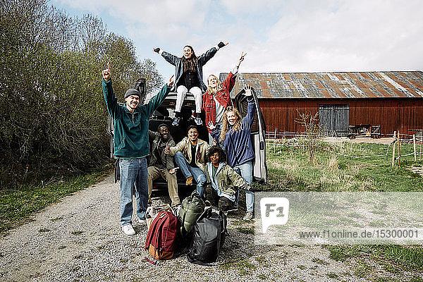 Porträt von aufgeregten Freunden und Freundinnen mit Gepäck vor dem Auto