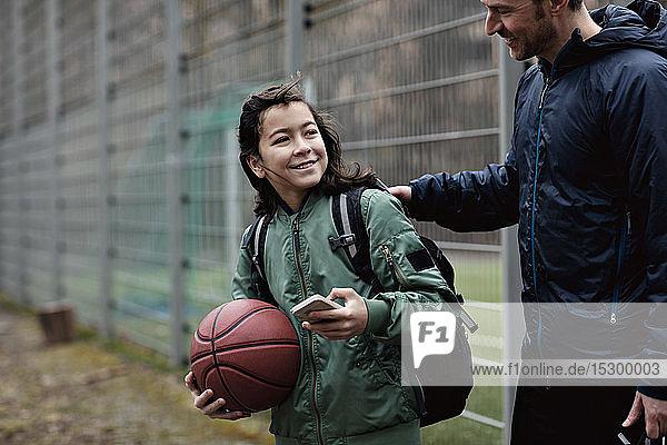 Lächelnder Sohn schaut den Vater an  während er auf dem Spielfeld steht