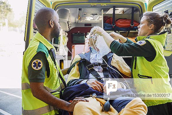 Männliche und weibliche Rettungssanitäter behandeln Geschäftsmann mit HLW außerhalb des Krankenwagens
