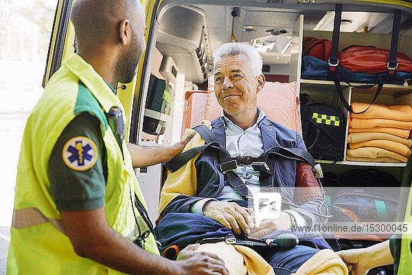 Männlicher Rettungssanitäter tröstet reifen Patienten im Krankenwagen