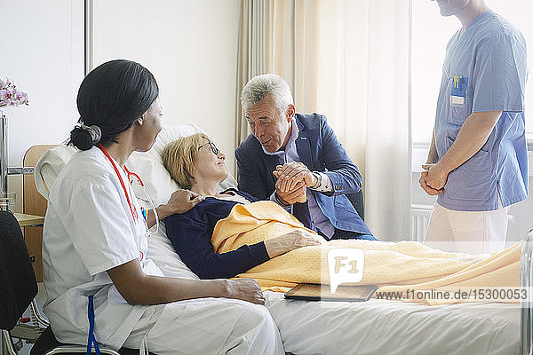 Healthcare workers looking at senior man consoling patient in hospital ward