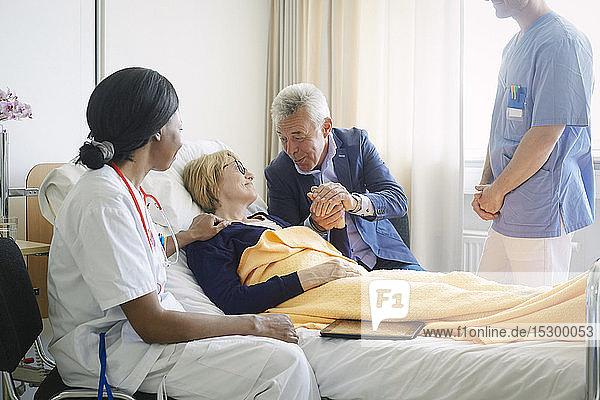 Mitarbeiter des Gesundheitswesens schauen auf einen älteren Mann  der einen Patienten auf der Krankenhausstation tröstet Mitarbeiter des Gesundheitswesens schauen auf einen älteren Mann, der einen Patienten auf der Krankenhausstation tröstet