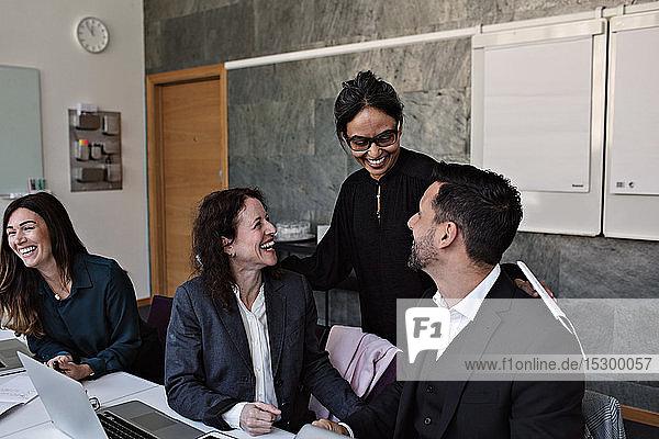 Lächelnde Geschäftsfrau interagiert mit fröhlichen Kollegen im Büro