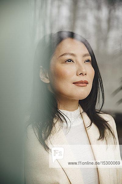 Zuversichtliche mittel-erwachsene Geschäftsfrau  die durch ein Fenster in ein Büro schaut