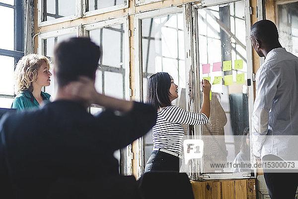 Geschäftsfrau schreibt auf Haftnotiz  während sie sich mit kreativen IT-Fachleuten im Büro trifft