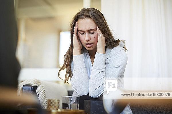Gestresster Teenager mit dem Kopf in der Hand im Gespräch mit Therapeutin im Workshop