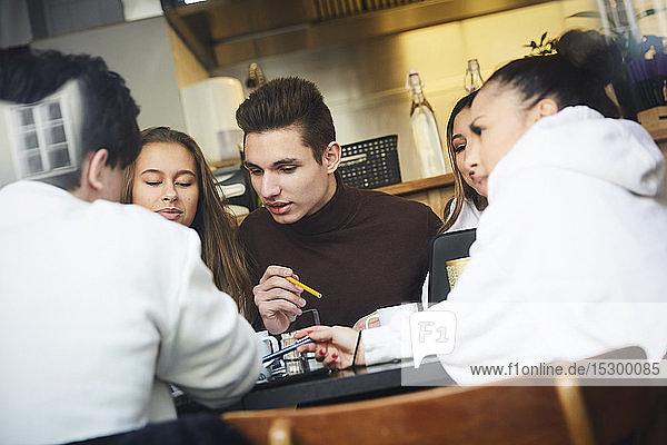 Männliche und weibliche Freunde im Teenageralter lernen bei Tisch im Café