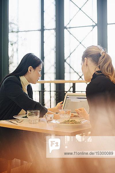 Zuversichtliche multiethnische Fachfrauen diskutieren am Laptop in der Büro-Cafeteria