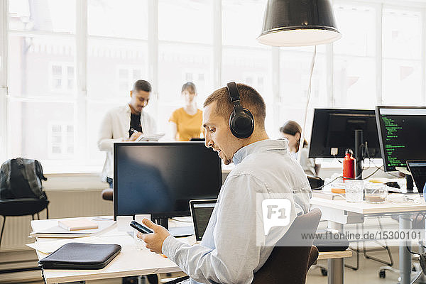 Side view of male engineer using mobile phone while coworkers working in background at creative workplace