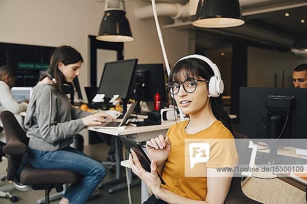 Porträt einer IT-Fachfrau  die mit einem digitalen Tablet arbeitet  während ihre Kollegen im Kreativbüro arbeiten