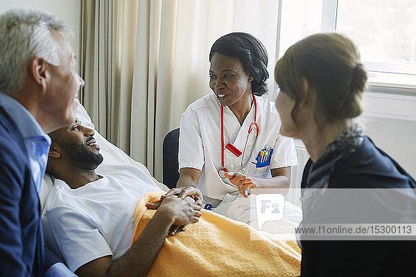 Mitarbeiter des Gesundheitswesens ermutigen Patient und seine Familie auf der Krankenhausstation