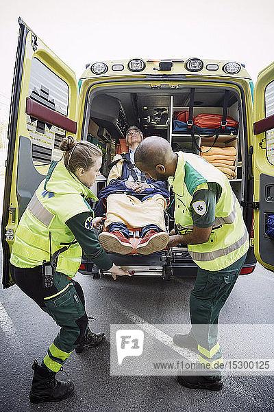 Männliche und weibliche Rettungssanitäter in voller Länge beim Entladen des Patienten aus dem Krankenwagen
