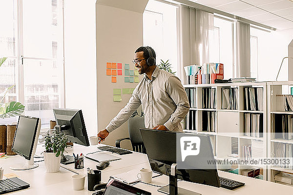 Smiling businessman with headphones looking away while standing in office