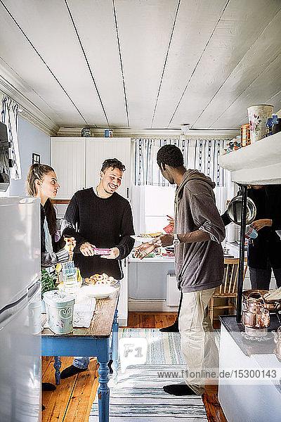 Glückliche Freunde unterhalten sich  während sie zu Hause in der Küche beim Essen stehen
