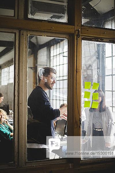 Junge Computerhacker bei Besprechung im Sitzungssaal mit Blick durch Glas am kreativen Arbeitsplatz