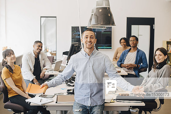 Portrait of smiling businessman gesturing while standing with colleagues sitting at desk in creative office