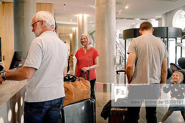 Lächelnde Familie steht an der Rezeption im Hotel