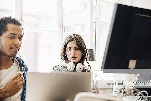 Computer programmers looking at laptop while programming in office
