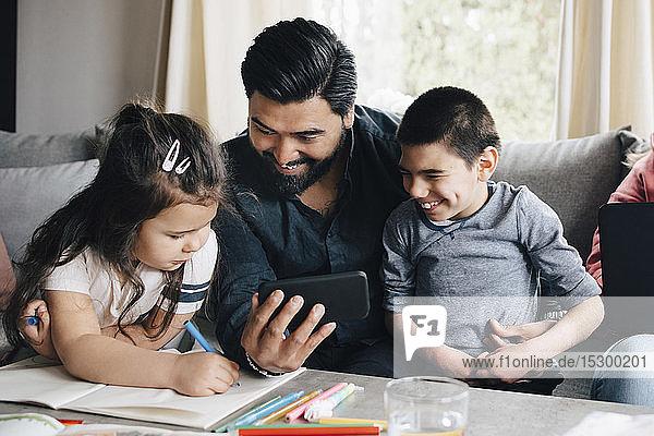Vater zeigt Kindern ein Handy  während eine Frau einen Laptop auf dem Sofa im Wohnzimmer benutzt Vater zeigt Kindern ein Handy, während eine Frau einen Laptop auf dem Sofa im Wohnzimmer benutzt