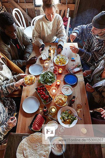Schrägaufnahme von Freunden bei Essen und Trinken  während sie in einer Hütte sitzen