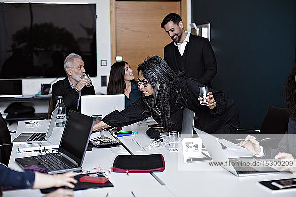 Business people working at conference table in board room at office