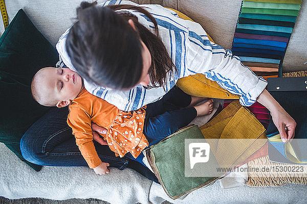 Hochwinkelansicht eines Design-Profis  der im Heimbüro mit seiner schlafenden Tochter auf dem Sofa sitzt Hochwinkelansicht eines Design-Profis, der im Heimbüro mit seiner schlafenden Tochter auf dem Sofa sitzt