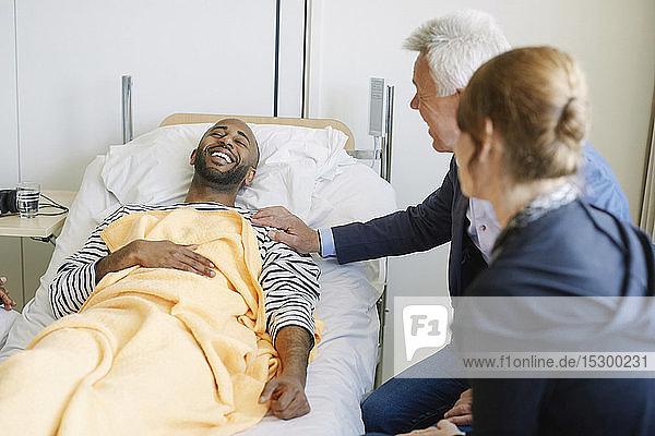 Vater ermutigt Sohn  während er auf der Krankenstation am Bett sitzt