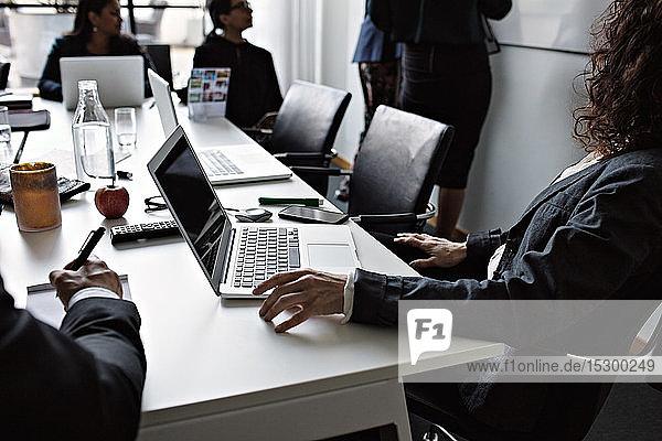 Geschäftsleute sitzen am Konferenztisch von weiblichen Kollegen  die während der Sitzung im Sitzungssaal stehen Geschäftsleute sitzen am Konferenztisch von weiblichen Kollegen, die während der Sitzung im Sitzungssaal stehen