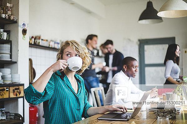 Junge Geschäftsfrau trinkt Kaffee  während Computerprogrammierer im Hintergrund im Büro arbeiten