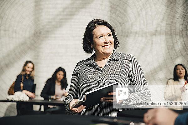 Lächelnde Geschäftsfrau sieht Geschäftsmann während einer Besprechung im Büro an
