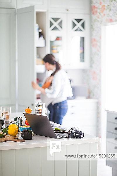 Berufstätige Mutter mit Tochter bereitet sich zu Hause in der Küche auf den Blog vor