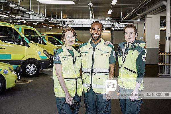 Porträt von männlichem und weiblichem Rettungswagenpersonal  die zusammen auf einem Parkplatz stehen