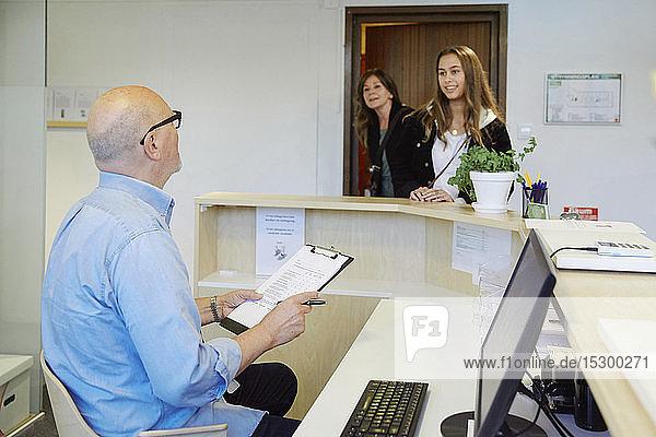 Männlicher Therapeut mit Klemmbrett  der im Wartezimmer mit dem Patienten spricht Männlicher Therapeut mit Klemmbrett, der im Wartezimmer mit dem Patienten spricht