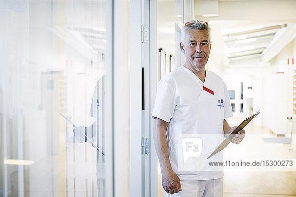 Porträt eines selbstbewussten leitenden Arztes  der ein Klemmbrett hält  während er im beleuchteten Korridor des Krankenhauses steht