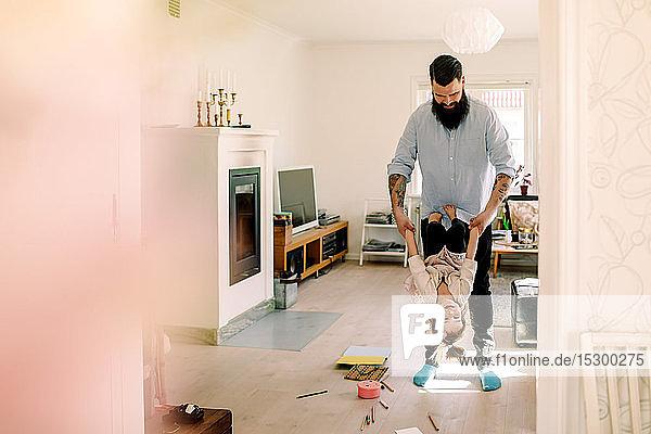 Mittelgroßer erwachsener Vater schwingt fröhliche Tochter im Wohnzimmer zu Hause