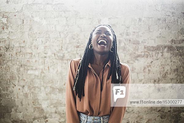 Weibliche Computerhackerin mit Dreadlocks  die im Büro gegen die Wand lacht Weibliche Computerhackerin mit Dreadlocks, die im Büro gegen die Wand lacht