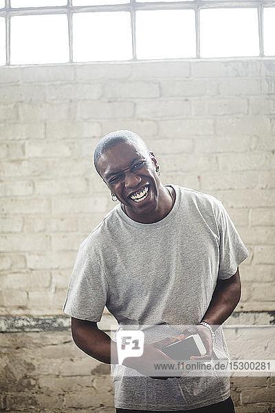 Porträt eines fröhlichen männlichen IT-Experten  der sein Handy in der Hand hält  während er im Büro an einer Ziegelmauer steht
