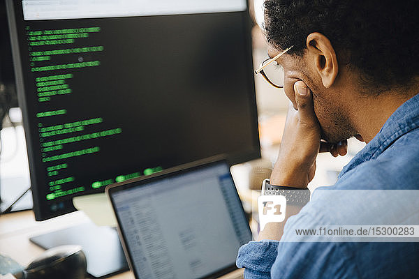 Fokussierter männlicher it-Profi  der einen Laptop benutzt  während er an einem kreativen Arbeitsplatz sitzt