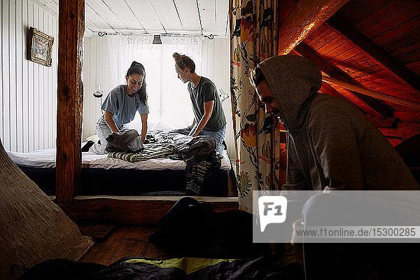 Männliche und weibliche Freunde falten Decken in einer Hütte Männliche und weibliche Freunde falten Decken in einer Hütte