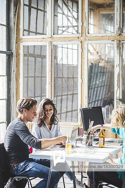 Junge Kreative  die im Sitzungssaal mit dem Laptop an innovativen Ideen arbeiten