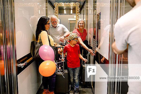 Frau drückt Knopf im Aufzug  während sie mit ihrer Familie steht