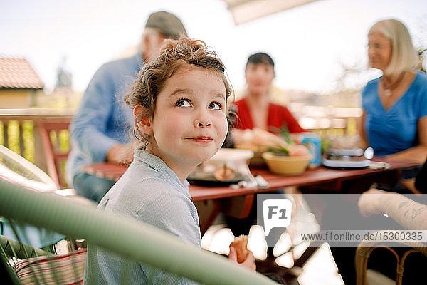 Lächelndes Mädchen schaut auf  während es mit der Familie am Tisch im Innenhof sitzt