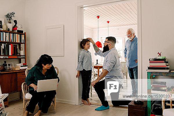 Familie schaut auf Mann  der die Größe seiner Tochter an der Wand an der Tür misst